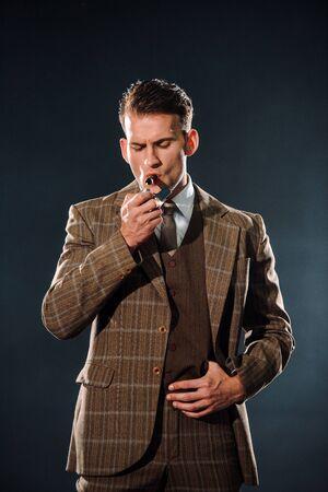 beau gangster en costume fumant un cigare sur fond noir Banque d'images