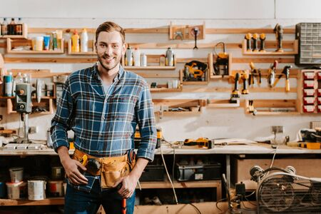 cheerful carpenter in apron standing and touching tool belt in workshop
