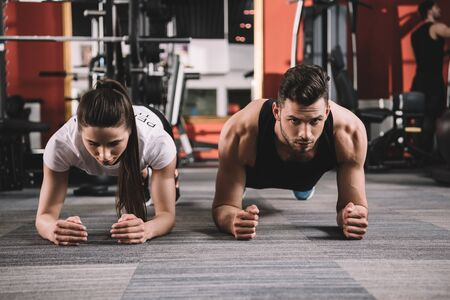 attractive trainer doing plank exercise together with handsome sportsman