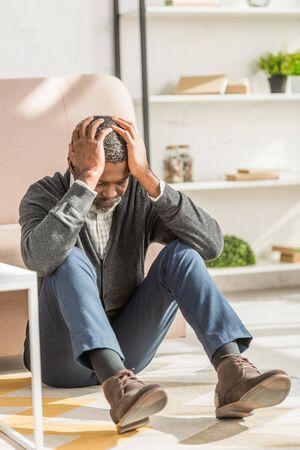 depressed african american man sitting on floor and suffering from migraine Standard-Bild