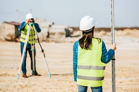 Selective focus of surveyor holding ruler and colleague with digital level on background Foto de archivo