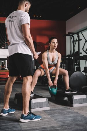 personal trainer supervising young sportswoman lifting weight in gym