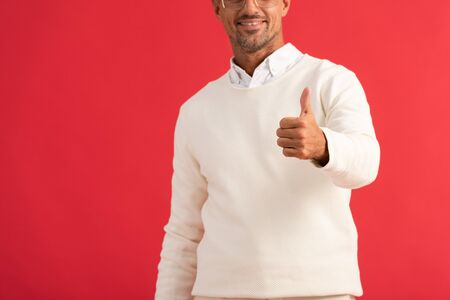 cropped view of cheerful man showing thumb up isolated on red