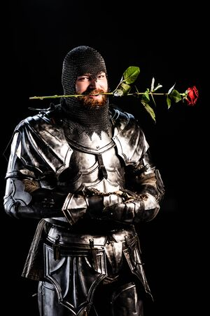 handsome knight in armor holding rose isolated on black