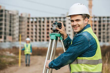 Enfoque selectivo del topógrafo sonriente con nivel digital y colega en segundo plano.