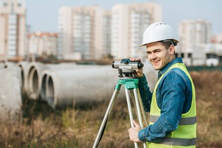 Surveyor with digital level smiling at camera with building materials at background Foto de archivo
