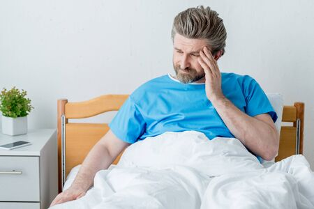 handsome patient in medical gown having headache in hospital