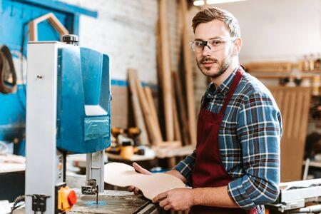 handsome carpenter holding wooden chopping board in workshop