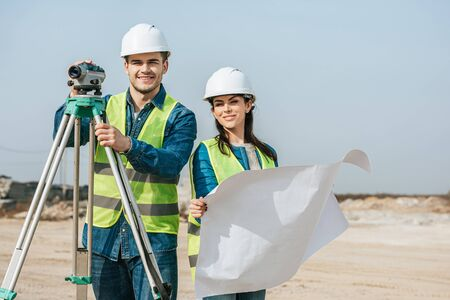 Smiling surveyors with digital level and blueprint looking at camera