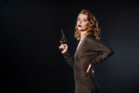 Chica peligrosa y atractiva sosteniendo la pistola mientras está de pie con la mano en la cadera aislado en negro