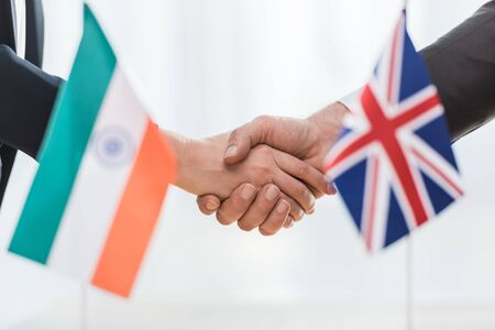 cropped view of diplomats shaking hands near flags of india and united kingdom