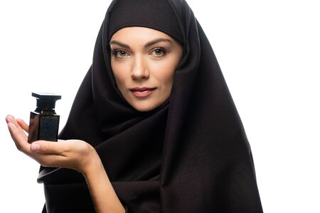 young Muslim woman in hijab holding bottle of perfume isolated on white Stock Photo
