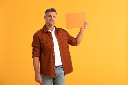 happy man holding blank speech bubble isolated on orange