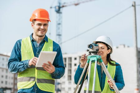 Smiling surveyors with digital tablet and measuring level on construction site