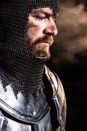 Apuesto caballero con armadura mirando a otro lado sobre fondo negro