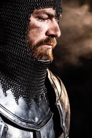 handsome knight in armor looking away on black background