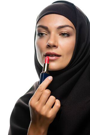 young Muslim woman in hijab applying red lipstick isolated on white Stock fotó