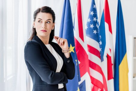 attractive diplomat looking away while standing near flags