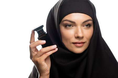 young Muslim woman in hijab holding bottle of perfume and looking away isolated on white