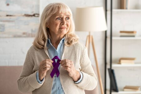 sad retired woman holding purple ribbon at home