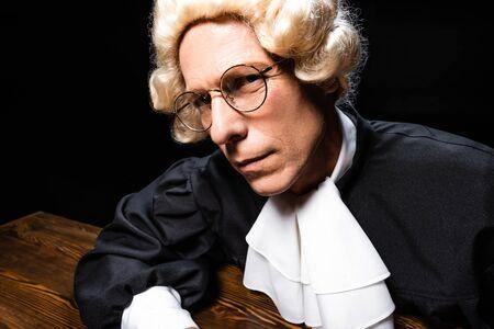 juge en robe judiciaire et perruque assis à table et regardant la caméra isolée sur fond noir Banque d'images