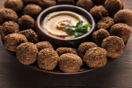close up view of falafel balls with hummus on plate on wooden table Stock Photo