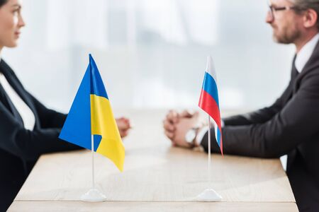 selective focus of ukrainian and russian flags near ambassadors with clenched hands