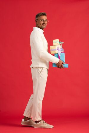 cheerful man in glasses holding gift boxes while standing on red Reklamní fotografie