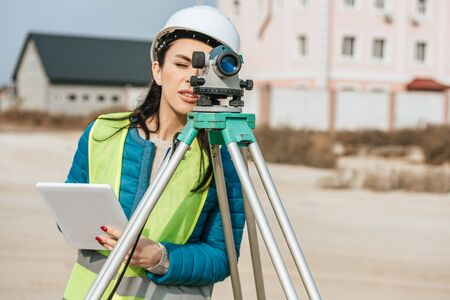 Female surveyor with digital tablet looking through measuring level Foto de archivo