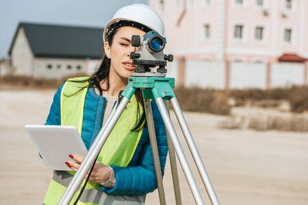 Topógrafo femenino con tableta digital mirando a través del nivel de medición Foto de archivo