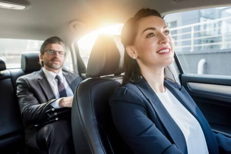 selective focus of attractive woman sitting in car with bearded diplomat