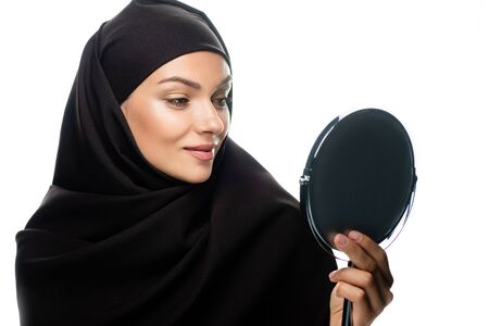 young Muslim woman in hijab looking at mirror isolated on white