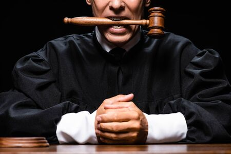 cropped view of judge in judicial robe sitting at table and holding gavel in mouth isolated on black
