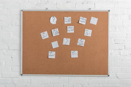 board with white papers with lettering near brick wall