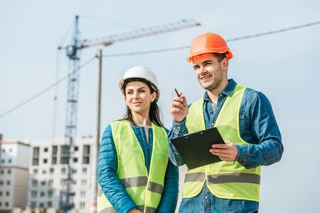 Smiling surveyor with clipboard pointing away to colleague on construction site