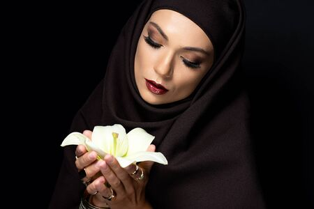 beautiful Muslim woman in hijab in golden rings and bracelet holding lily isolated on black