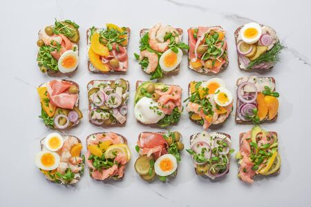 top view of danish smorrebrod sandwiches on white marble surface