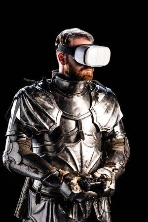 Kiev, Ucrania - 9 de octubre de 2019: caballero con casco de realidad virtual en armadura sosteniendo joystick sobre fondo negro
