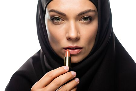 young Muslim woman in hijab applying beige lipstick isolated on white