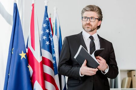 bearded diplomat holding folder near flags