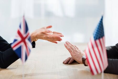 cropped view of diplomats gesturing near flags of america and united kingdom