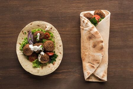 top view of falafel with vegetables and sauce wrapped and unwrapped in pita on wooden table