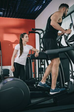 attentive trainer supervising sportsman working out on stepper in gym Stock Photo