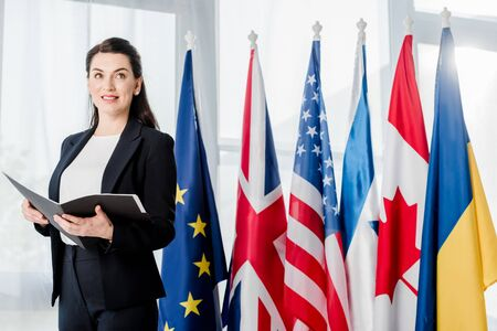 cheerful ambassador holding folder near different flags