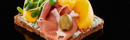 panoramic shot of ham and canned peaches on danish smorrebrod sandwich on black Foto de archivo - 134656945
