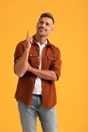 cheerful man pointing with finger and looking up isolated on orange
