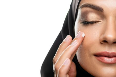 cropped view of young Muslim woman in hijab applying facial cream with closed eyes isolated on white Stock fotó
