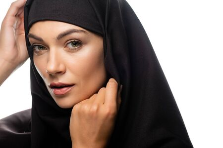 beautiful young Muslim woman in hijab with hands near face isolated on white