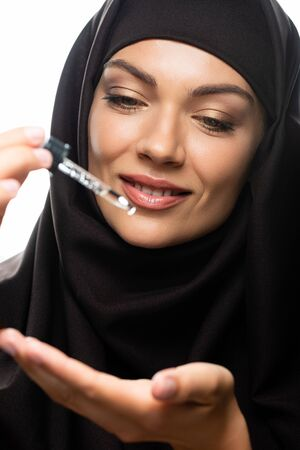 smiling young Muslim woman in hijab holding dropper with serum isolated on white
