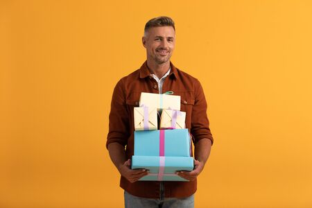 handsome man smiling while holding gift boxes isolated on orange
